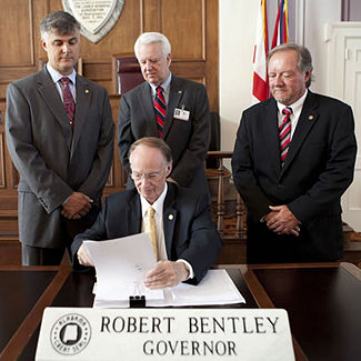 Governor Bentley signs the act into law while Scott Beason, Kerry Rich and Micky Hammon look on