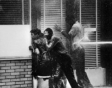 Four youths pinned to a wall by spray from a firehose in an iconic photography by Charles Moore of Black Star